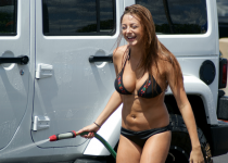 Girl in black bikiny washing brand new jeep wrangler in summer, while she is laughting